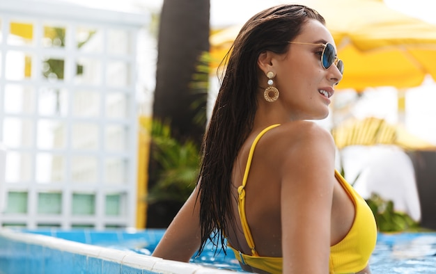 Rear-view of elegant attractive woman in yellow bikini, lean swimming pool edge.
