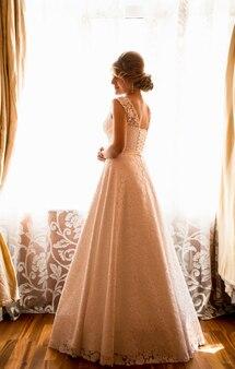 Rear view of elegant bride posing at window in hotel room