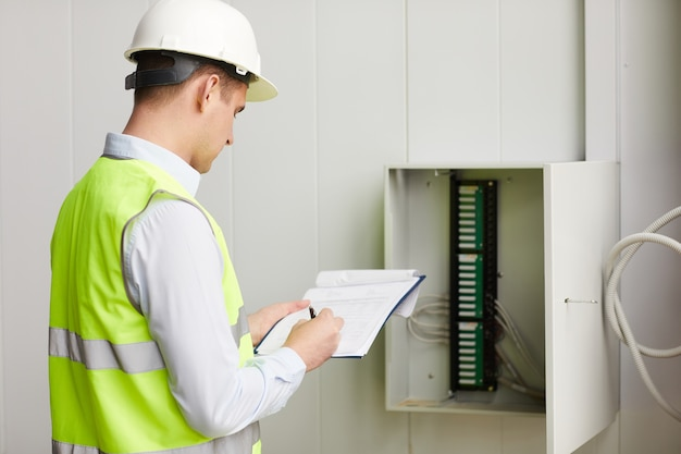 Rear view of engineer in reflective vest making notes in document he checking the data of electricity meter
