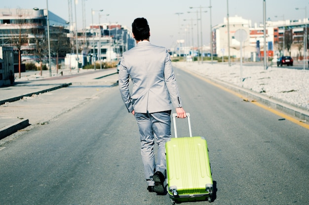 Rear view of executive with green suitcase