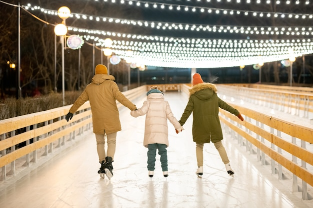 Rear view of family of three in skates holding hands and skating together on skating rink outdoors