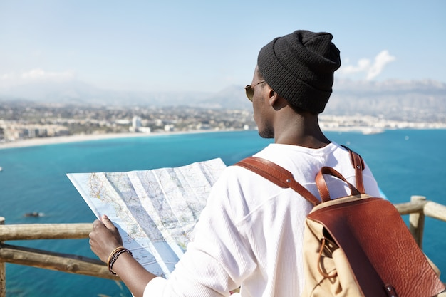 Rear view of of fashionable afro american hiker with leather backpack on his shoulders holding paper guide, reading information about beautiful places and locations in front of him along sea coast