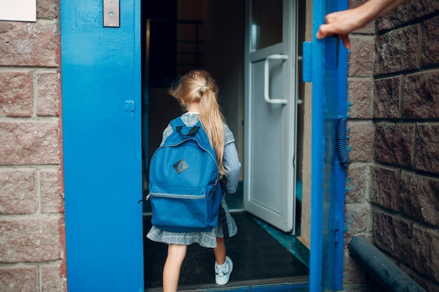 Rear view of father come back to home from school with his daughter carrying backpack.