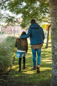Rear view of a father and daughter walking on grass