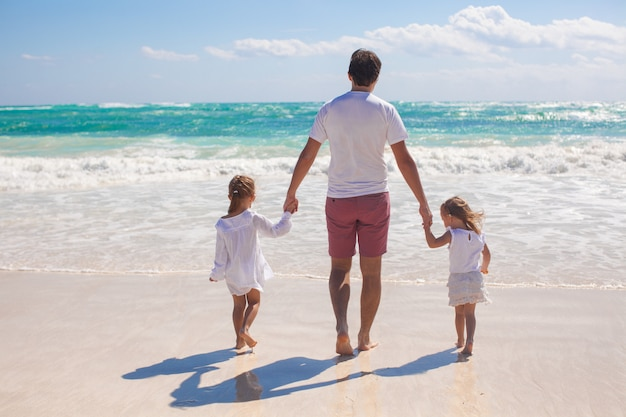 Rear view of father and his two cute daughters walking on white sand beach