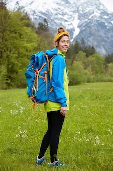 La retrovisione del viaggiatore con zaino e sacco a pelo femminile cammina sui piedi sul prato verde contro il paesaggio della montagna, trasporta grande zaino