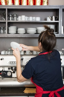 Rear view of female barrister arranging saucers in the shelves
