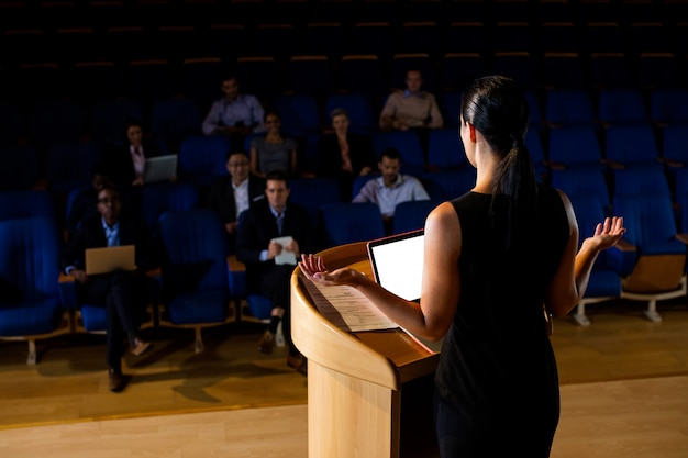 Rear view of female business executive giving a speech