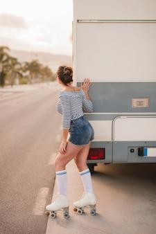 Rear view of a female skater standing near the caravan peeking on road