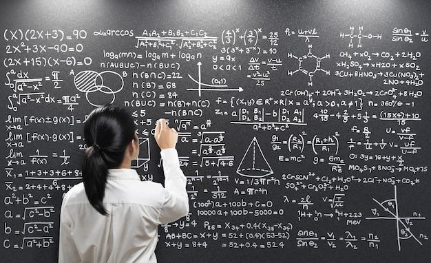 Rear view female teacher write on blackboard