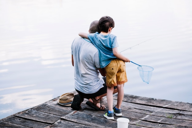 Rear view of a fisherman with his son fishing on lake
