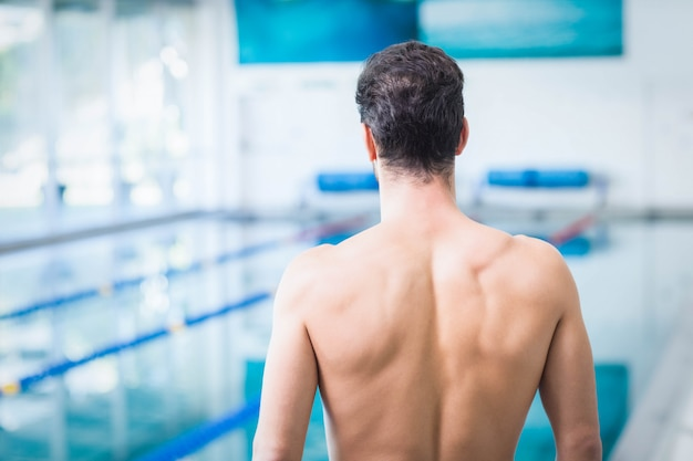 Rear view of fit man standing in front of the pool