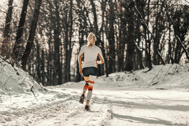 Rear view of fit sportswoman running on snowy path in nature at winter. sports, cardio exercises, winter fitness