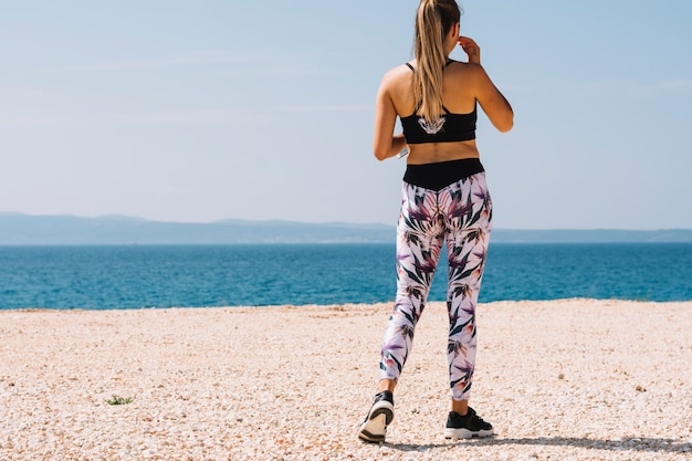 Rear view of a fitness young woman standing at beach