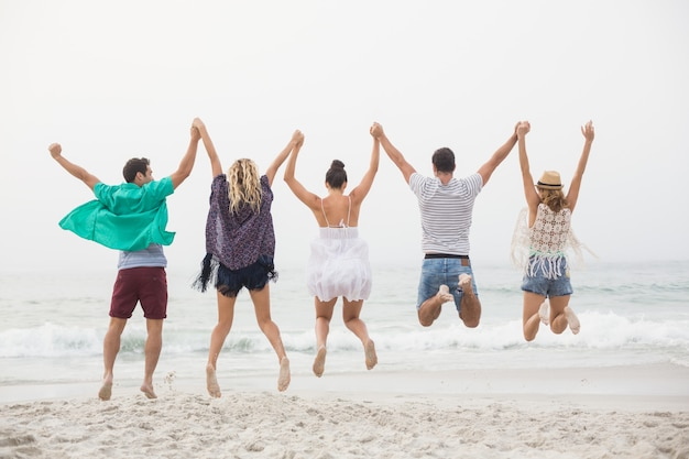 Rear view of friends holding hands and jumping on the beach