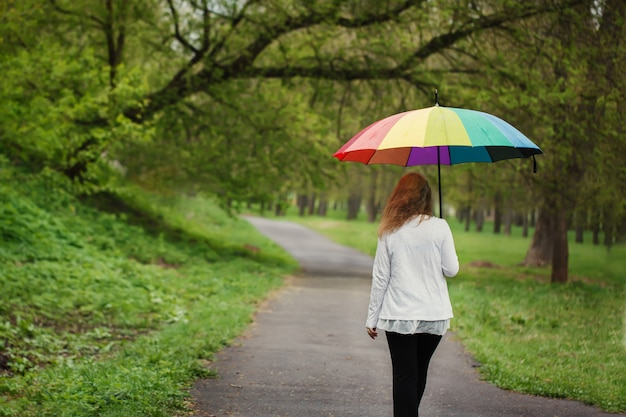 Rear view of girl under a bright umbrella, walking in rain
