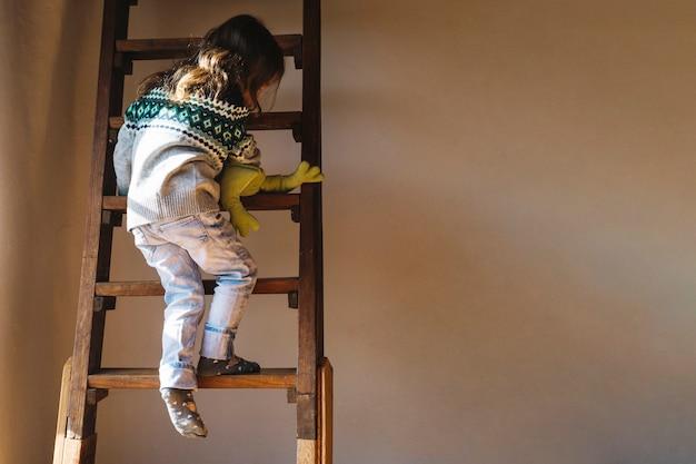 Rear view of a girl climbing ladder