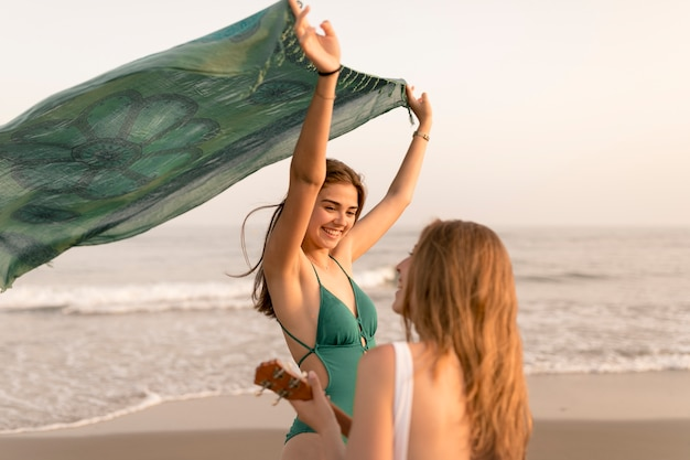 Rear view of girl playing ukulele for her friend holding scarf at beach