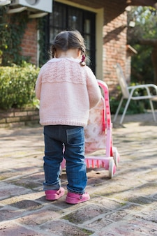 Rear view of a girl playing with stroller outside the house