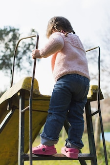 Rear view of a girl standing on slide ladder in the park
