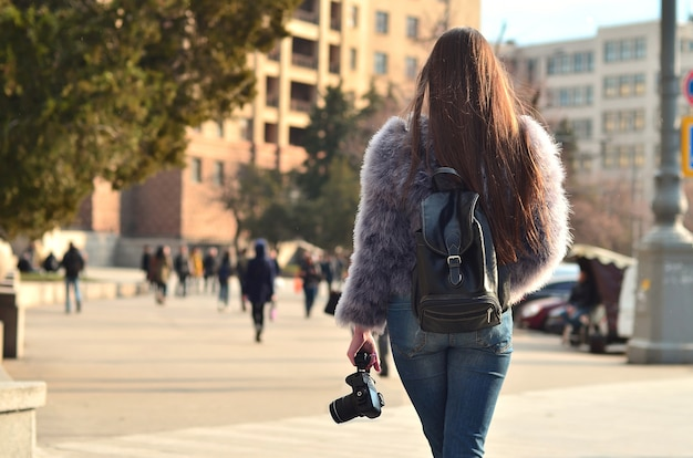 Rear view of a girl with a digital camera on a crowded street ba