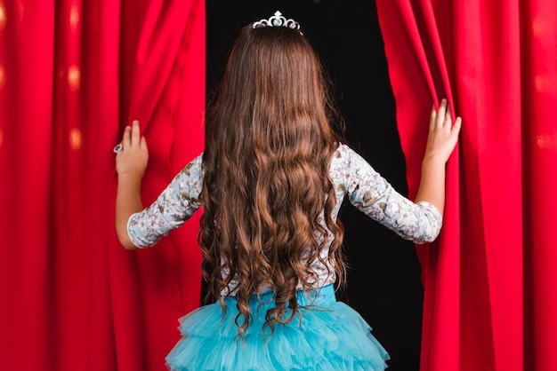 Rear view of girl with long brunette wavy hair looking from red curtain