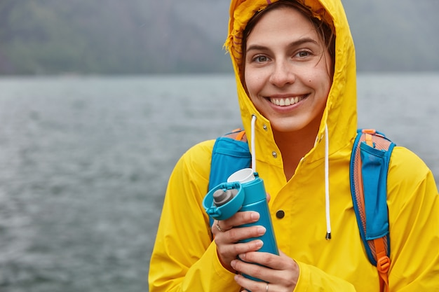 Rear view of glad woman wears yellow raincoat with hood, smiles happily, walks on shore of mountain lake