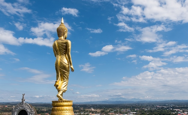 Rear view of the golden standing buddha statue in the traditional thai style located in the viewpoint on the high mountain
