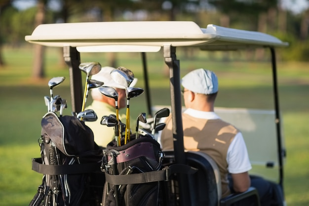 Rear view of golfer friends sitting in golf buggy