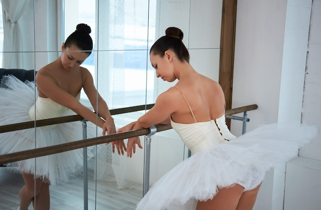 Rear view of gorgeous ballerina in tutu leaning on barre while warming up. copyspace