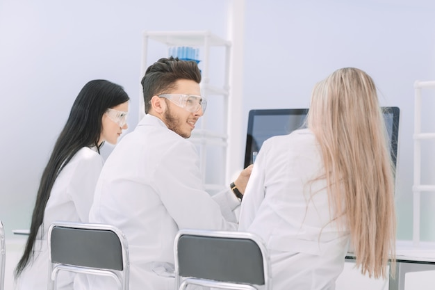 Rear view.a group of scientists look at the computer monitor . science and health