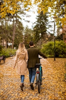 Rear view at handsome young couple in the autumn park with electrical bicycle