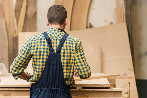 Rear view of a handyman working in the workshop