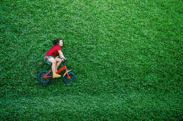 Rear view of a happy asian kids. girl on bicycle lay down at green lawn in summer day