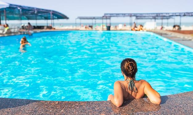 후면보기 행복 한 작은 십 대 소녀는 수영장의 가장자리에 기대어 호텔에서 휴식을 취하는 동안 뜨거운 여름 태양 광선 아래에서 깨끗한 따뜻한 물을 즐깁니다. 프리미엄 사진