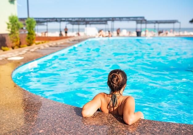 후면보기 행복 한 작은 십 대 소녀는 수영장의 가장자리에 기대어 깨끗한 따뜻한 물을 즐깁니다
