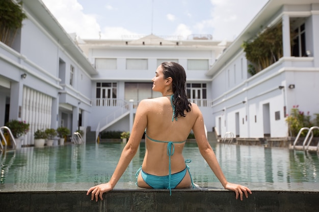 Rear view of happy woman resting at hotel pool