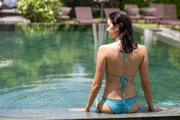 Rear view of happy woman at spa swimming pool