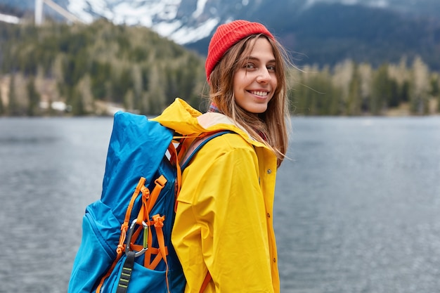 Rear view of happy young european woman enjoys nice serene day, nature landscape scenery, carries rucksack