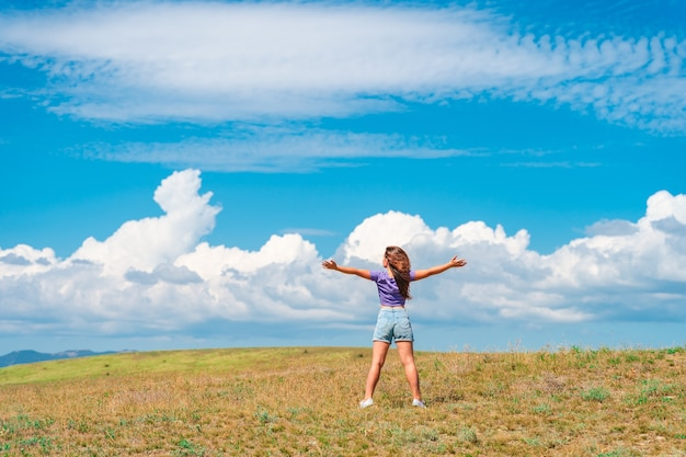Rear view of a happy young woman standing with her arms open against a blue sky with clouds