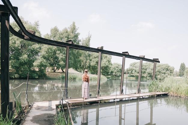배면도. 호수 위에 다리를 걷고 있는 히피 소녀. 자연과의 일체감 개념