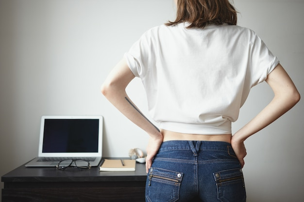 Rear view of hipster girl wearing blue jeans and blank white t-shirt with copyspace for your text or promotional content indoors. people, style, fashion, modern technology and clothing design concept