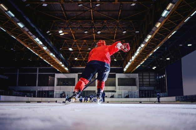 Rear view of hockey player skating towards opposite team and trying to score. hall interior.