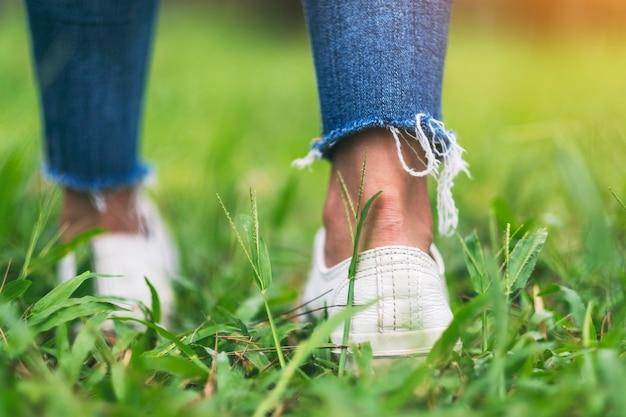 Изображение заднего вида ног, идущих по зеленой траве