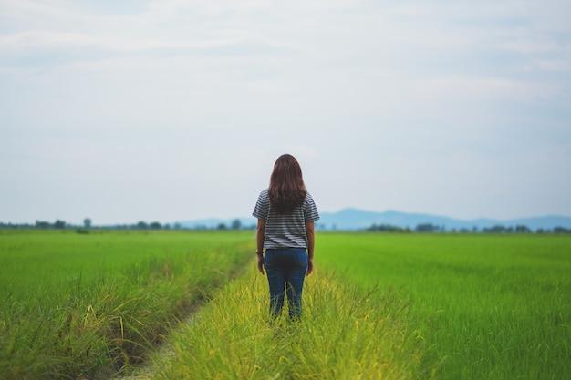 편안하고 차분한 느낌으로 서서 아름다운 논을 바라보는 여성의 뒷모습 이미지