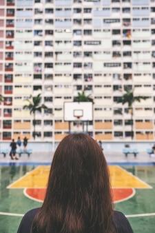 홍콩에서 빈티지 스타일 파스텔 색상 건물을 가진 여성의 후면 보기 이미지