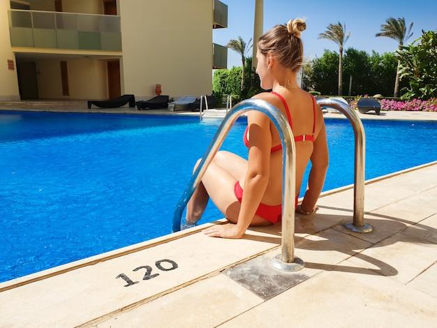 호텔 리조트에서 수영장에 앉아 빨간 비키니 입은 아름 다운 섹시 한 젊은 여자의 후면보기 이미지. 편안 하 고 여름 휴가 휴가 동안 좋은 시간을 보내고 여자.