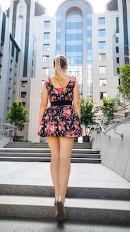 도시 거리의 돌계단을 걸어가는 짧은 드레스를 입고 긴 다리를 가진 아름다운 젊은 여성의 후면 이미지