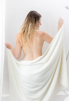 Rear view image of sexy woman covering in towel at bathtub