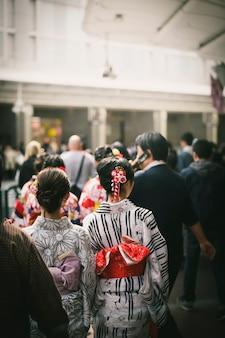Rear view of japanese women in yukata among the crowd